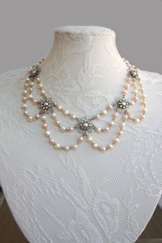 Choker necklace features seven silver-plated filigree flowers set with pink freshwater pearls surrounded with Swarovski AB rhinestone and connected between each flower with curled eye pins white freshwater pearls and powder pink freshwater pearls.