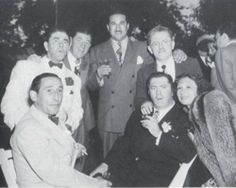 The boys at Joan's  (Moe's daughter) wedding. Curly is the one on the right, sitting in the chair. Moe is the one standing up on the left, and Shemp is between him and another man. Their brother Irving (I think) is standing behind Curly.