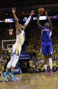 Los Angeles Clippers' Jamal Crawford, right, makes a 3-point basket over Golden State Warriors' Andre Iguodala during the first half in Game 3 of an opening-round NBA basketball playoff series Thursday, April 24, 2014, in Oakland, Calif. (AP Photo/Marcio Jose Sanchez)