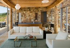 sustainable home in Big Sur- love the exposed wood beams and natural stone wall
