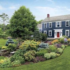 12 Upkeep Ideas To Add Curb Appeal (diversity of plants and flowers planted in a dramatic entry garden)