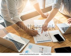 Close-up of female and male hands pointing at turnover graph while discussing it on wooden desk in office. group concept.