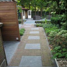 tuinpad van klinkers en tegels, daarachter van dezelfde tegels een terras