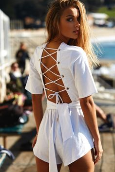 Obsessed with the details, the Backless Ballari Playsuit is made from a linen blend fabric in a fresh white. It is a backless style and features gold eyelet and lace up detailing at back, 1/2 length sleeves, a plunging V neckline and an elasticated waistband. Complete the look with the included matching waist tie and black flats or boots! By Sabo Skirt.