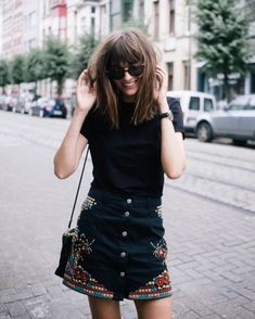 Button skirt, black top, sunglasses and a smile.