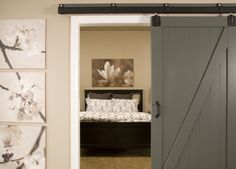 Beautiful grey sliding barn doors leading to a bedroom- Would love the barn doors for the entrance of the master bedroom!