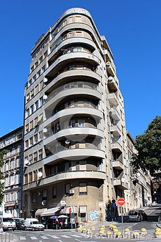 Tall narrow concrete building with large round balconies situated on street corner in Rijeka, Croatia.