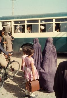 Title: Setting Off. Description: Two Afghan Women, and their daughters, wait in a queue to board a bus in the Capital. Location: Kabul, Eastern Afghanistan.
