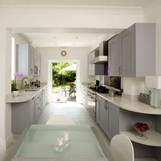 The layout of this galley-style kitchen combines elegance with convenience. The doors at the end lead directly into the garden, which on a warm day extends the kitchen by bringing the outside in. The cool grey of the units, which makes the space feel so open and light, is warmed up by the injection of vibrant purple on the splashback.