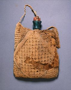 Pilgrim's flask in an embroidered linen bag 14th - 15th century (1301 - 1500) Material and technique glass flask, probably blown; linen bag, with remains of embroidery in blue thread, probably cotton or flax; drawn-thread openwork; bag stuffed with vegetable fibre Dimensions with bag 13.5 x 11 x 1.5 cm sight size (height x width x depth) flask 10.2 cm (height) Accession no. EA1994.113