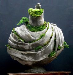 Draped ruined bust overgrown with moss