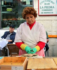 A woman shucking oysters in Vigo, Spain.