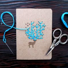 """CuriousDoodles embroidery kits combine traditional embroidery techniques with modern designs that are fun for all levels. Tap into your crafty spirit this holiday and stitch up an impressive antler rack. The notebook holes are laser cut to make it easier to sew (like connect the dots). Each kit contains 2 notebooks, quality teal thread, & 1 needle * Notebook size: 3.5""""x 5"""" * Cover- Kraft paper 100% recycled * Inside- Blank white paper 100% recycled * 32 pages"""
