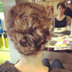 Soft messy bun with pieces around the face