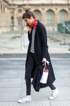 A French street style look to try now: top knot, red bandana neck scarf, striped tee, long coat or jacket, skinny black jeans and hi-top Converse sneakers.