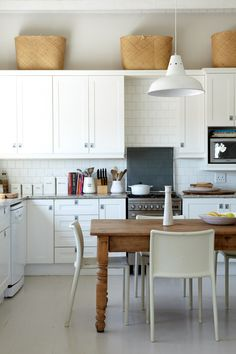 a chic neutral Scandinavian kitchen with vintage cabinets, a white tile backspla. a chic neutral Scandinavian kitchen with vintage cabinets, a white tile backsplash, a rustic wooden Classic Kitchen, Rustic Kitchen, Kitchen Dining, Kitchen Decor, Kitchen White, Kitchen Stove, Dining Table, Country Kitchen, Kitchen Interior