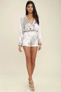 Follow your heart right to the Dream Chaser Silver Long Sleeve Romper! Sleek, and slightly stretchy, metallic woven fabric falls from a collared neckline to a surplice bodice (with modesty snap), and long button cuff sleeves. Elasticized waist and breezy shorts.
