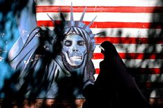 In this Tuesday, Sept. 25, 2007 file photo A veiled Iranian woman walks past graffiti art characterizing the U.S. Statue of Liberty, painted on the wall of the former U.S. Embassy in Tehran, Iran.