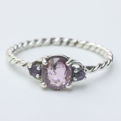 Oval faceted pink spinel ring with amethyst side set gems in prongs setting with sterling silver oxidized twist band