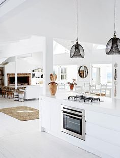 A stunningly beautiful home in Grotto Bay, South Africa, set on a headland with amazing views over the ocean. All white and weatherboard, with vaulted ceilings and white wood floors, and natural timbe