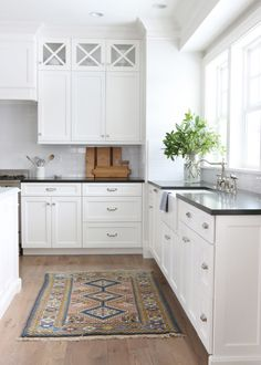 Traditional white kitchen with black countertops. Love the white subway tile and x-shape upper cabinets. #kitchendesign #kitchens #design #whitekitchen #homedecor #homedesign #homedecorideas