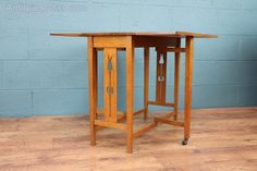An Arts and Crafts drop leaf table, c1905. Made of solid oak, drop leaves to each side with legs on original castors, decorative tulip piercings to each side. In good restored condition.