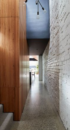 White painted brick and wood line this hallway in a renovated house.