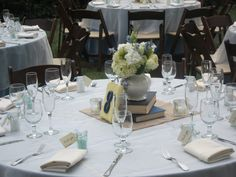 Book Centerpiece - looks like an actual wedding, not a styled shoot. 2 books, white vase