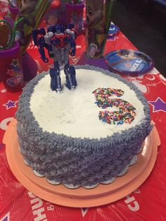 Easy Optimus prime cake. Use a transformer top as a cake topper and decorate the rest of the cake as desired