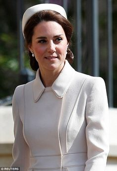 Classic look: Kate wore her brown locks swept back in a low chignon with a matching cream ...