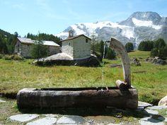 Nos verões as vacas são levadas para os prados de alta montanha para pastagem. Pequenas aldeias de verão, como esta mostrada nesta foto tirada em Savoie são usadas. A fonte e a capela Santa Clara na aldeia de Le Monal em Sainte-Foy-Tarentaise em Haute-Tarentaise no Parque Nacional de Vanoise, em Savoie, França.