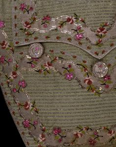Most of the patterning on this glittering 1770s waistcoat has been fashioned during the weaving of the silk fabric. The fabric was known as a silver tissue, and incorporated an additional weft of silver thread woven in with the green silk warp and weft. This created the silver stripe and wavy silver border seen on the pocket and hem of the waistcoat. Additional colours in the weave produced the red and white flowers and green stems.    Once off the loom, further decoration was added to the…