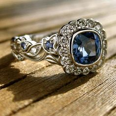 Vintage-style vine engagement ring with blue sapphire & diamonds. Gem specs: 1.27 ct natural, blue sapphire, 6.00 x 5.98 mm square cushion cut. Blue sapphires are set in flower buds, halo and leafs have diamonds. Cast in platinum, showing vine in great detail with plain section for