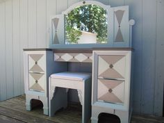 Vanity upcycled with custom paint job, new stool, mirror and custom designed wood accents.