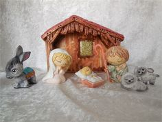 So delightful - sweet childrens faces on this holy family complete with stable, donkey and two little lambs - seven pieces in all. The stable measures approximately 8W x 6H. Mary, Joseph and donkey are approximately 3H with Baby Jesus and lambs being smaller. #13   This nativity scene has been hand painted using a premium ceramic stain, spray sealer, metallic paints, glitter.   Would make a great gift for a nativity collector or to use in your home during the holiday season.   Prompt…