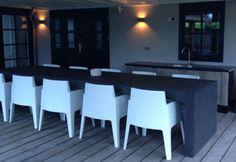 Donkergrijze betonlook buitentafel. Stoere combinatie met witte boxstoelen. www.molitli-interieurmakers.nl