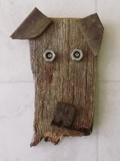 Dog face made from scraps of old rusty and weathered objects like bolts, leather straps and barn wood pieces.