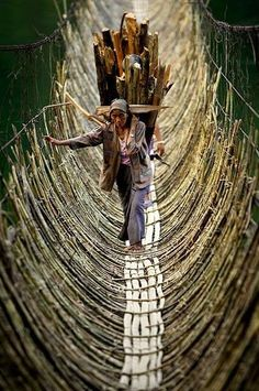 Porters crossing a hanging bridge, Himalaya.
