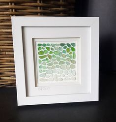 """""""One of a kind signed artwork"""" with sea glass combed from the beautiful beaches of Cornwall, UK. Each piece is collected by me. The piece is a delicate mix of green shades, and whites, and would make a lovely gift for any occasion. *PLEASE NOTE THAT THIS IS A FRAMED ORIGINAL - Framed in a white recessed/box frame Frame Size approx: 7"""" X 7"""" (depth 1"""") - the frame has a stand, and a hook to hang on your wall. All images Œ© Cathy Shimmen THIS WILL BE SENT USING A TRACKED AND SIGNED FOR SERVICE…"""