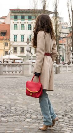 Fashion Blogger Veronika Lipar of Brunette from Wall Street wearing ripped blue Levi's jeans, off-white double breasted Weekend Maxmara coat, red dangling belt, blush Gianvito Rossi plexi pumps, See by Chloe pink top handle bag, blue leather gloves standing on the street of Ljubljana
