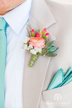 I dont like the bouttineire but this is an idea of colors. The guys wearing charcoal grey, tiffany blue ties, and light coral for the rose.