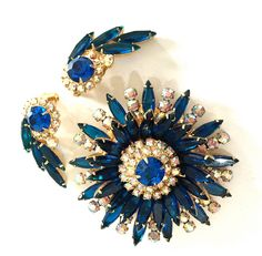 This is a gorgeous Juliana D&E Sunburst brooch and clip-on earring demi from Vintage Imagine What a wonderful set with Capri blue navettes forming a beautifully tiered brooch and matching clip-on earrings. The iridescents of the aurora borealis are such a sparkling accent to the stunning deep blue stones. This brooch has so many of the key Juliana design qualities, the figure 8s, open and closed stones, great crystal rhinestones, and the tiered design to name a few. The set is in Very, Ve...