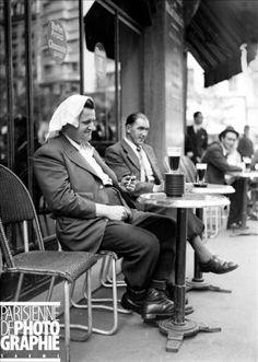 Une victime de la vague de chaleur, devant une pile de soucoupes, correspondant au nombre de ses consommations. Paris, juin 1941.