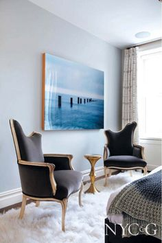 Blue artwork in neutral living room with dark and glamorous, traditional armchairs