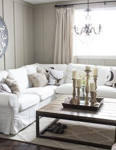white slipcovered sectional, oversize clock, board and batten wall, chandelier, large coffee table