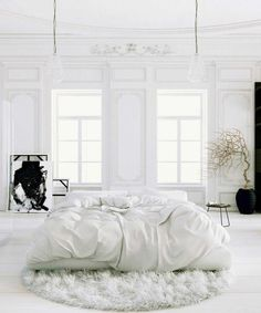 Love the space and white walls, crumpled sheets and moon shaped rug minus the dead plant
