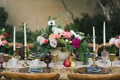 A neutral compote allows vibrant flowers to take center stage in this gorgeous centerpiece by Jessica Kettle. To add fall hues to the pastel color palette, surround the flower arrangement with pears and matte gold candlestick holders.