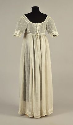 LOT 87 FRENCH EMBROIDERED MULL DRESS, 1805 White cotton having empire bodice with short sleeve, embroidered with curved bands of moss roses and foliage to the front hem and sleeve, center panel and upper sleeve embroidered with small star flowers, drawstring neckline with scalloped embroidery, three back buttons between two drawstrings. DLM tag. B-34, L 46-48. (Scattered small holes, few period mends, tear at hem, cluster of small spots above hem border) good.