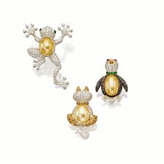 SET OF THREE GEM-SET, CULTURED PEARL AND DIAMOND BROOCHES Comprising: a penguin with a body pavé-set with black diamonds and a cultured pearl belly, a seated cat, the posterior body composed of a golden cultured pearl, and a frog similarly-set with brilliant-cut diamonds with accentuated webbed hands and feet, a golden cultured pearl body, and cabochon emerald-set eyes, mounted in 18 karat white gold.