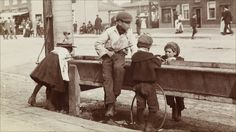 A new exhibition at the Museum of London showcases over 200 candid images of everyday life from London's streets spanning 150 years from 1860. An early sepia-toned (above) ahows children playing at a water trough in Barnet High Street, c.1900.